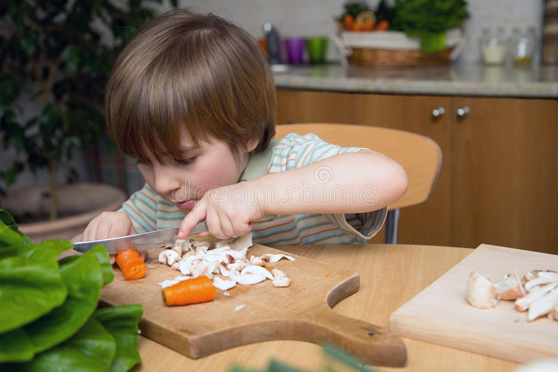 在一个木板的用左手的男孩切口红萝卜非常小心地在厨房里 免版税图库摄影