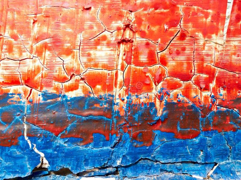 在一个木板的破裂的红色和蓝色油漆 免版税图库摄影