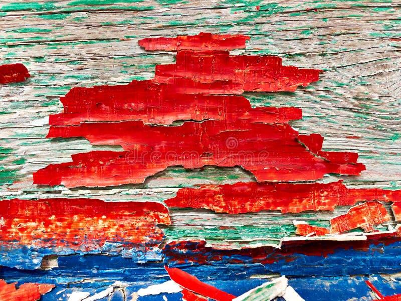 在一个木板的破裂的红色,蓝色和绿色油漆 免版税库存图片