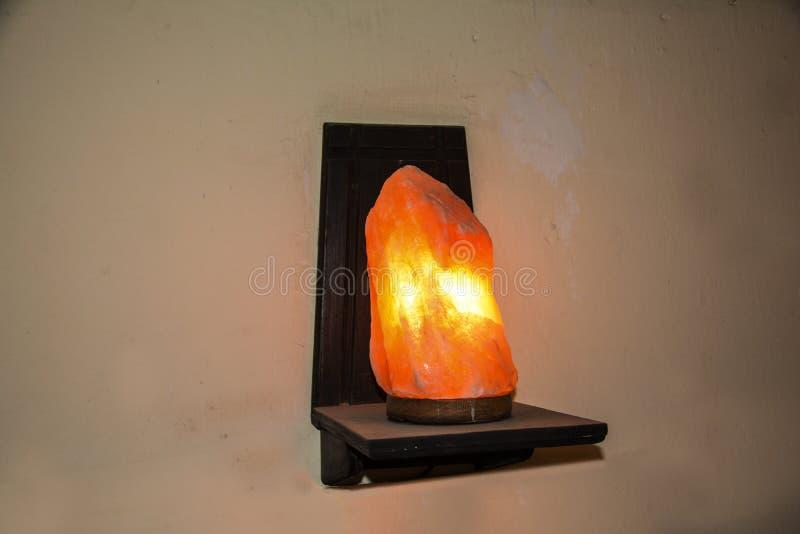 在一个木架子托架的自然盐灯 喜马拉雅盐 免版税库存图片