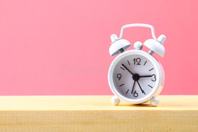 在一个木架子的白色小闹钟在桃红色淡色背景 简单派 库存照片