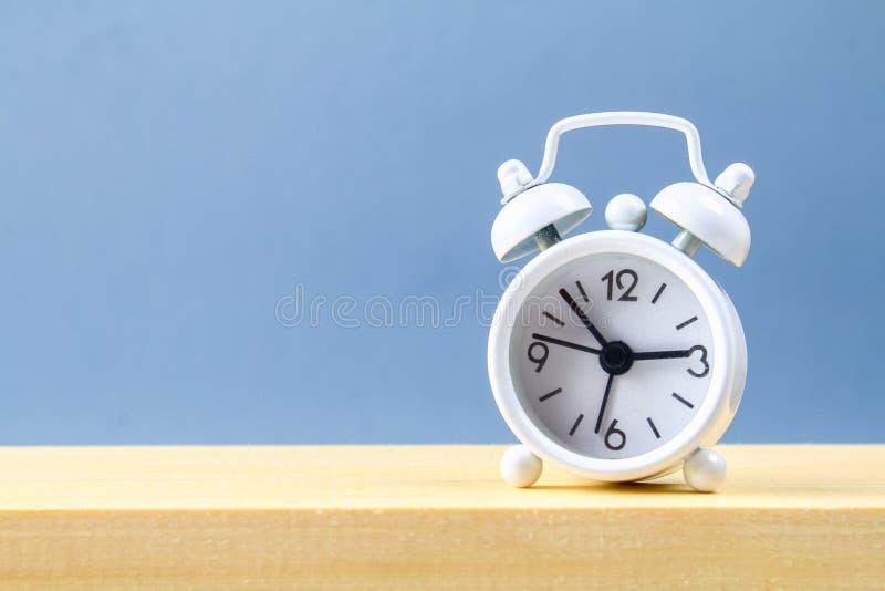 在一个木架子的白色小闹钟在灰色淡色背景 简单派 图库摄影