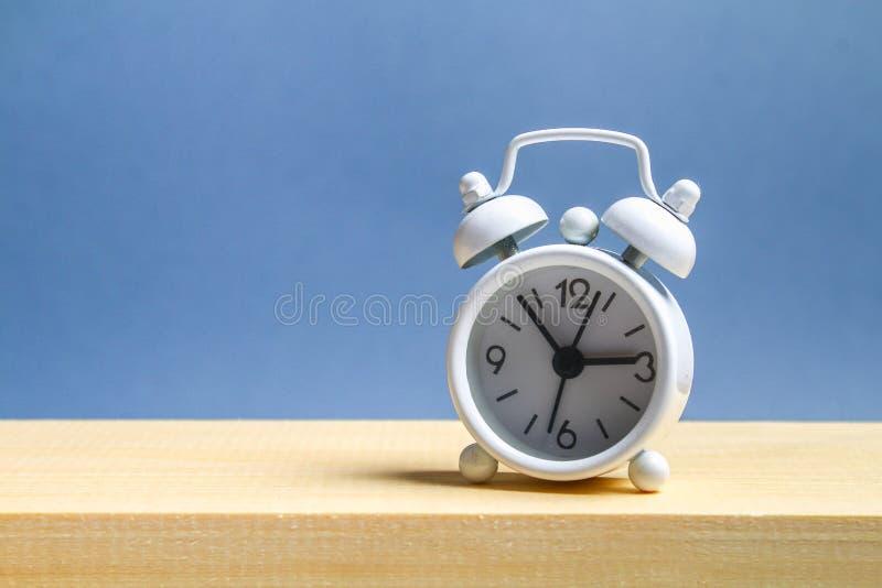 在一个木架子的白色小闹钟在灰色淡色背景 简单派 库存图片