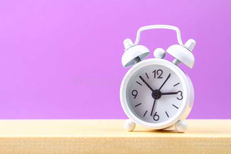 在一个木架子的白色小闹钟在紫色淡色背景 简单派 免版税库存照片