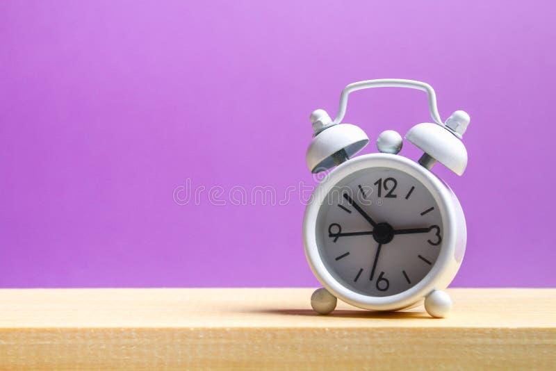 在一个木架子的白色小闹钟在紫色淡色背景 简单派 免版税图库摄影