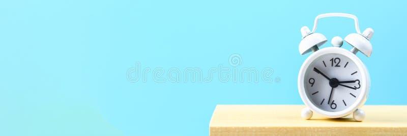 在一个木架子的白色小闹钟在蓝色淡色背景 简单派 库存照片