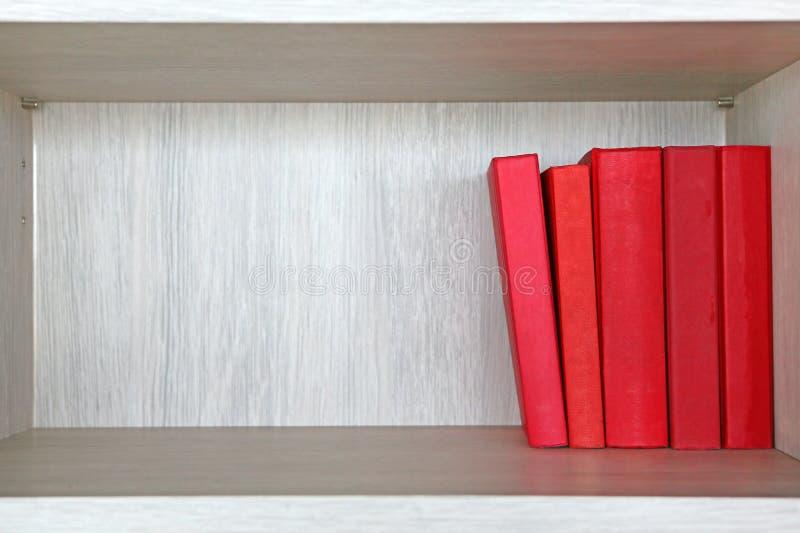 在一个木架子的红色书 免版税库存照片