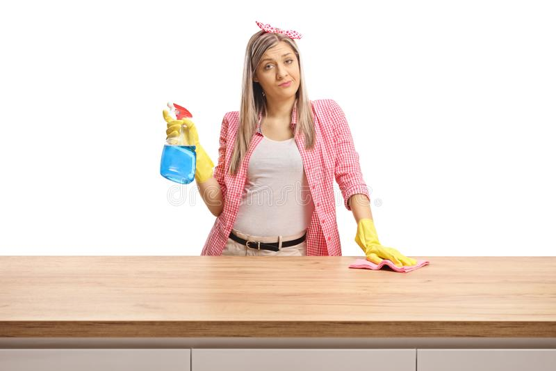 在一个木柜台后的年轻女人厌烦  免版税库存图片
