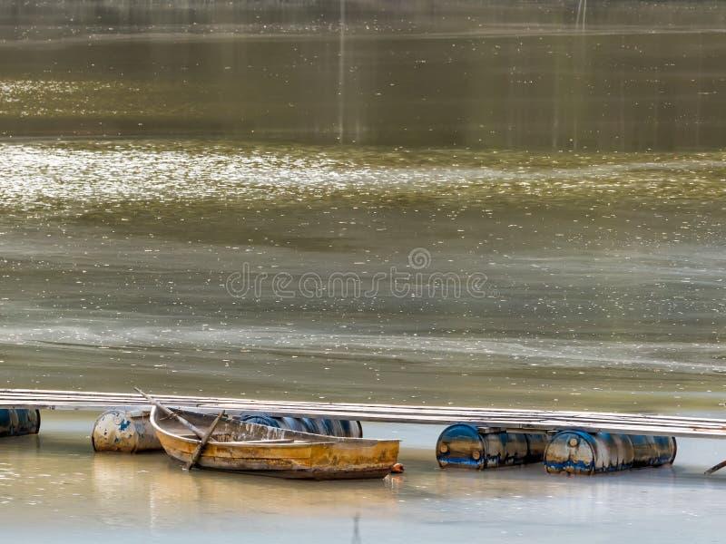 在一个木桥附近的一条老小船在湖 免版税库存照片