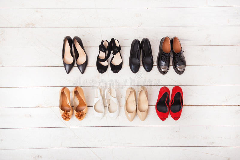 在一个木白色地板上的不同的夏天妇女` s鞋子 在视图之上 免版税库存图片