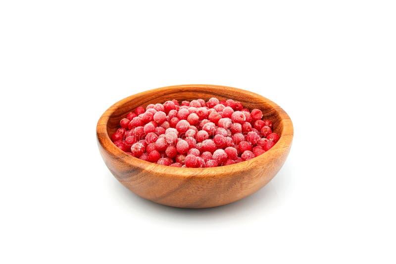 在一个木碗的冷冻红色海鼠李莓果 图库摄影