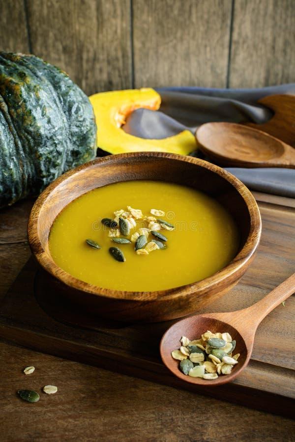 在一个木碗的南瓜汤用新鲜的南瓜 免版税库存图片