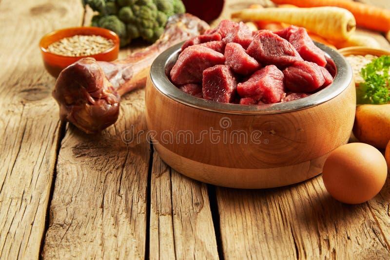 在一个木碗的宠物食品用新鲜的肉 免版税库存照片