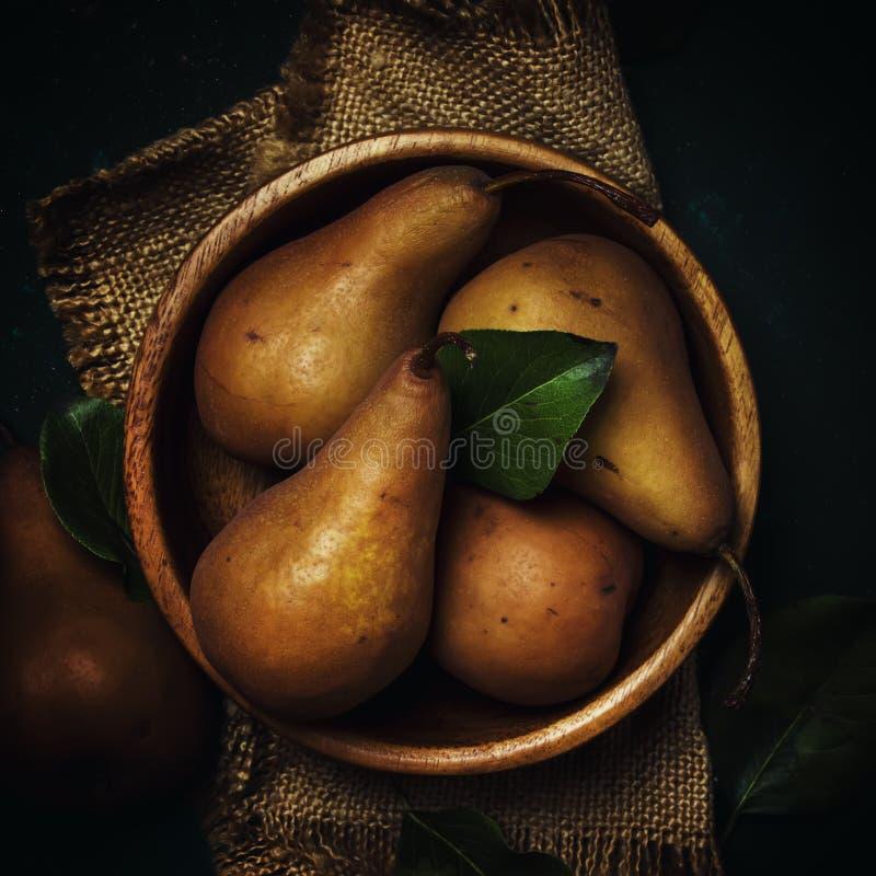 在一个木碗的成熟棕色梨,黑暗的背景,土气样式 库存照片
