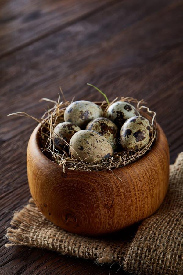 在一个木碗的新鲜的鹌鹑蛋在黑暗的木背景,顶视图,特写镜头 库存照片