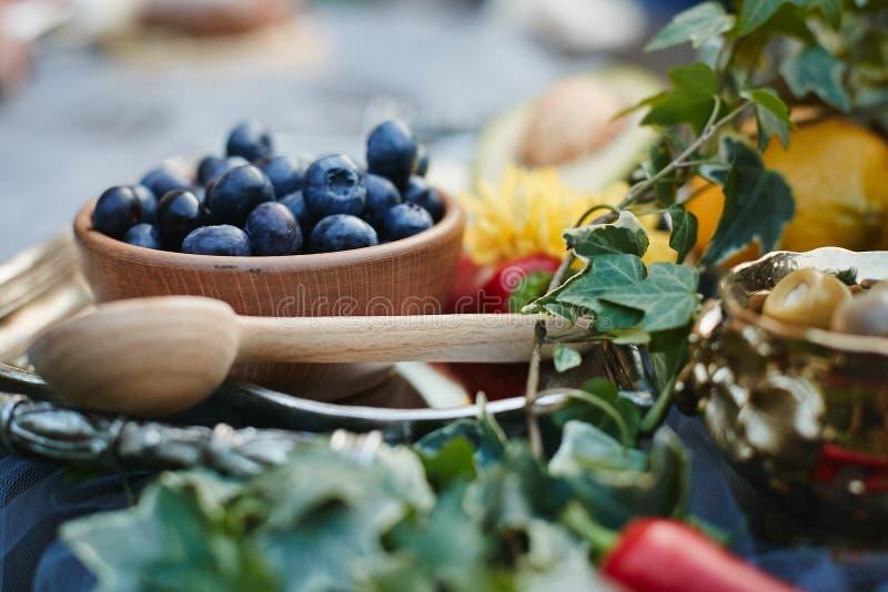 在一个木碗的新鲜的黑橄榄在木匙子附近 免版税库存图片