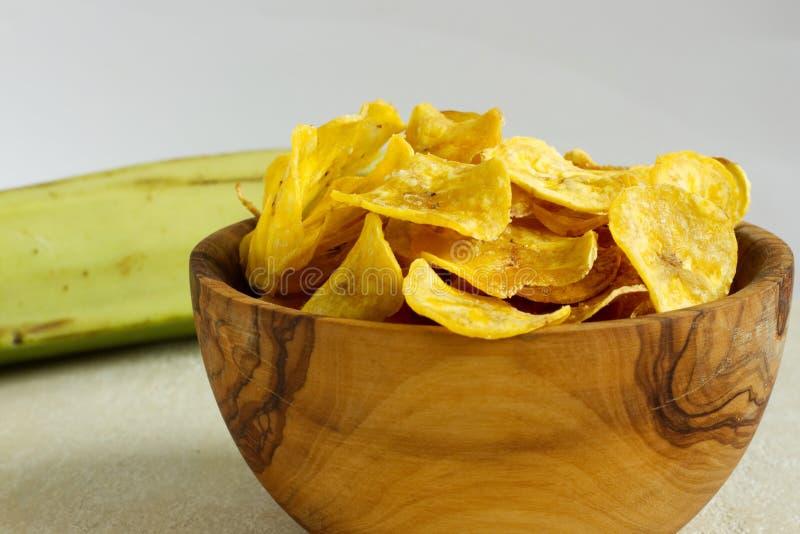 在一个木碗的油煎的大蕉芯片 库存图片