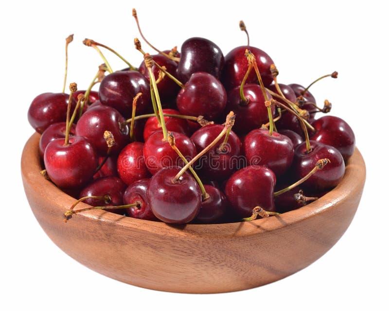 在一个木碗的红色樱桃在白色 免版税库存照片