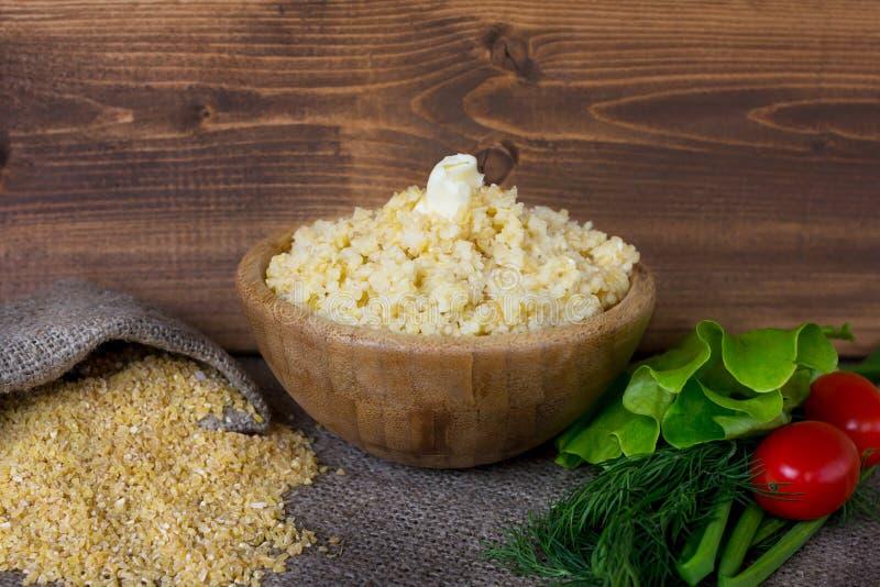 在一个木碗的麦子沙粒 免版税库存图片