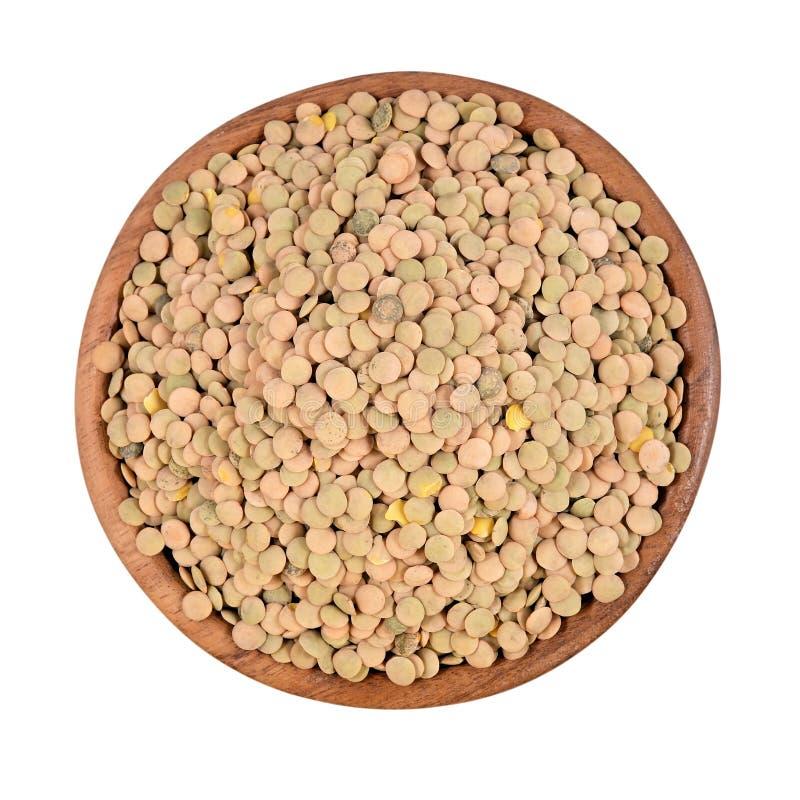 在一个木碗的绿色未加工的扁豆在白色背景 图库摄影