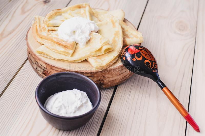 在一个木立场的俄国稀薄的薄煎饼由与酸性稀奶油的自然木头制成 Maslenitsa是Maslenitsa食物节日 免版税库存照片