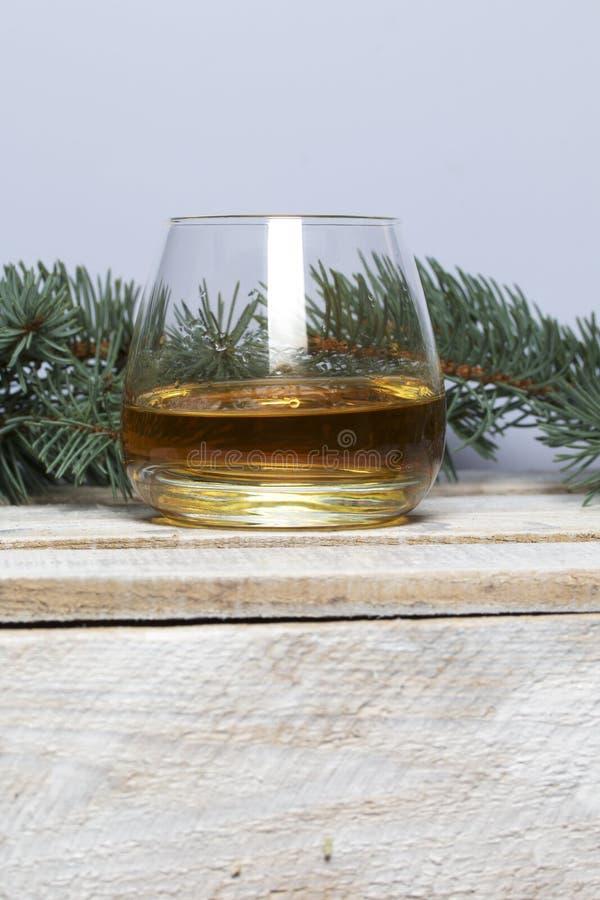 在一个木箱的蓝色云杉的分支委员会,绘在白色 附近一杯威士忌酒 免版税图库摄影