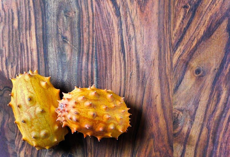 在一个木背景的两异乎寻常的kiwano果子 库存照片