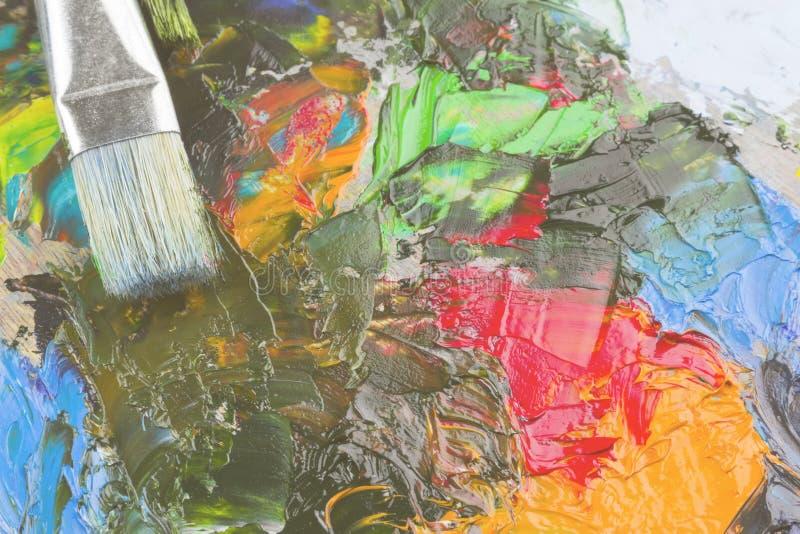 在一个木调色板和刷子的各种各样的艺术油漆 定调子 免版税库存照片