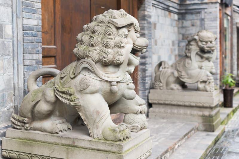 在一个木门前面的两个狮子石雕象在中国 免版税图库摄影