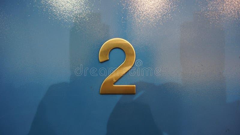 在一个木门的金属房间号码第二 库存图片