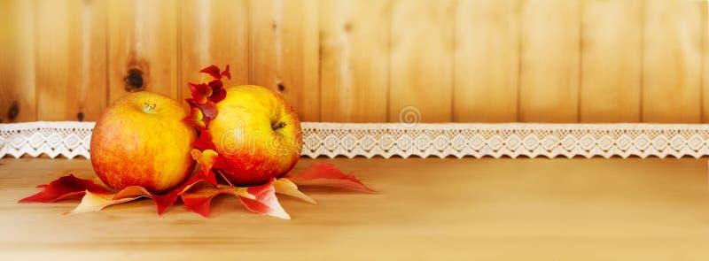 在一个木餐具柜的两个苹果 免版税库存照片