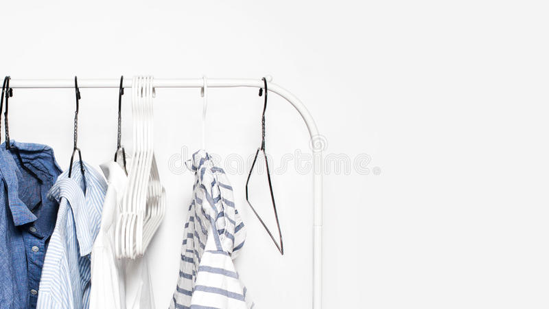 在一个机架的被剥离的衣裳在白色墙壁背景结束u 免版税库存图片