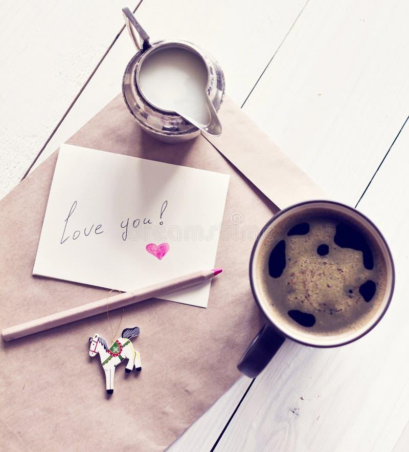 在一个杯子和牛奶与卡片和信封的无奶咖啡与wotds 免版税库存图片