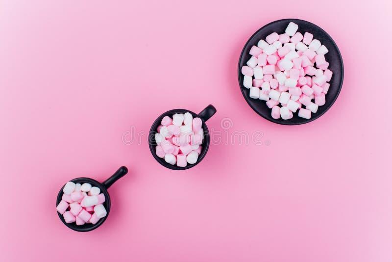 在一个杯子的淡色蛋白软糖在桃红色背景 免版税库存图片