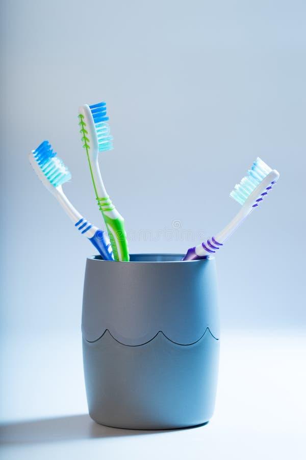 在一个杯子的牙刷在蓝色背景 图库摄影
