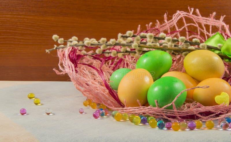 在一个柳条筐和杨柳分支的复活节彩蛋 图库摄影