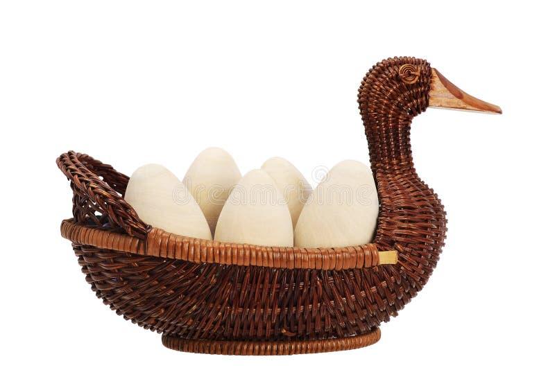 在一个柳条筐的复活节彩蛋 鸭子柳条 木鸡蛋 免版税库存照片