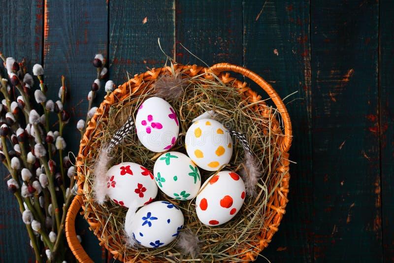 在一个柳条筐的复活节彩蛋在木桌上 免版税库存图片