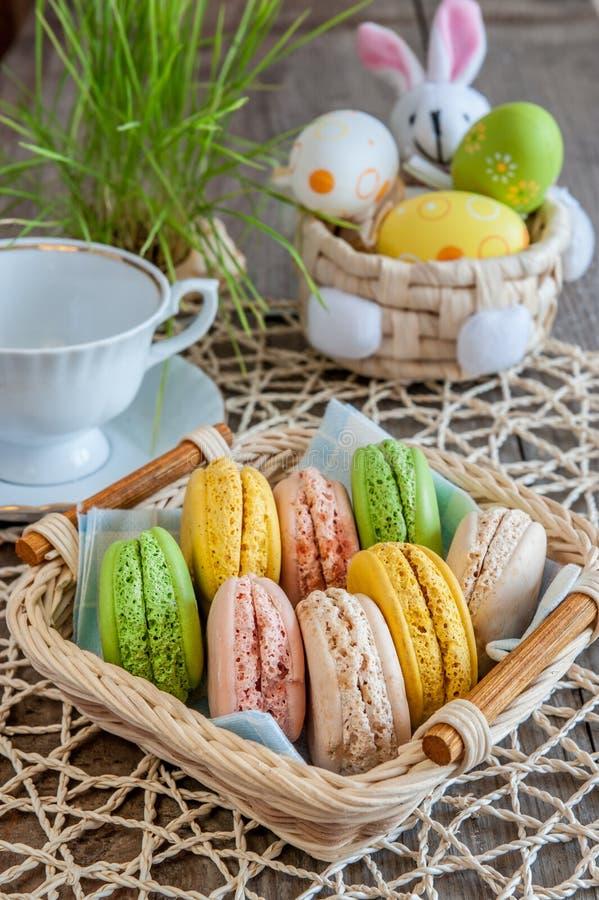 在一个柳条筐的多彩多姿的蛋白甜饼蛋白杏仁饼干用白色杯和复活节彩蛋 免版税库存照片