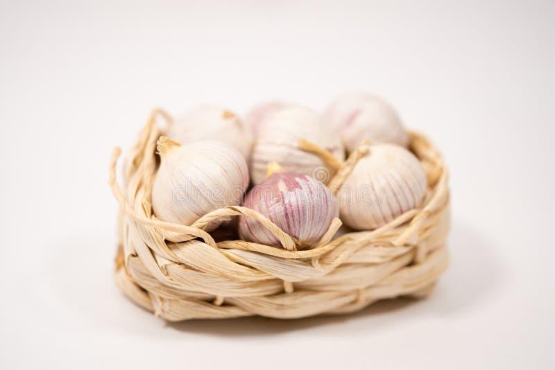 在一个柳条筐的大蒜,在白色背景 干法国大蒜 红色大蒜 库存照片