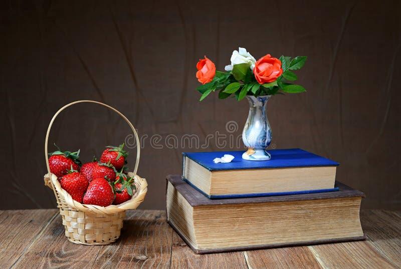 在一个柳条筐的新鲜的在花瓶的草莓和花 免版税库存照片