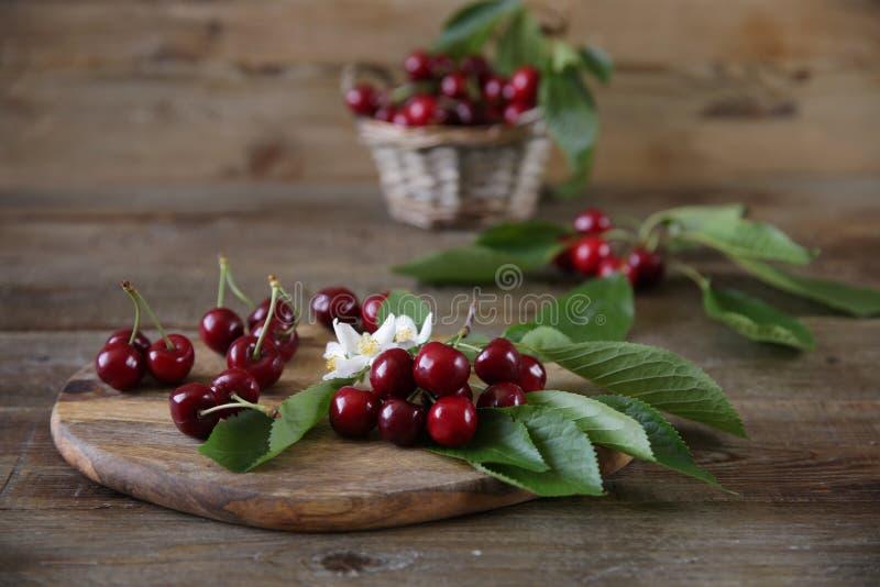 在一个柳条筐的新鲜的有机樱桃与叶子和白花在木土气背景 r ?? 免版税库存图片