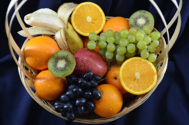 在一个柳条筐的果子在深蓝织品背景 免版税图库摄影