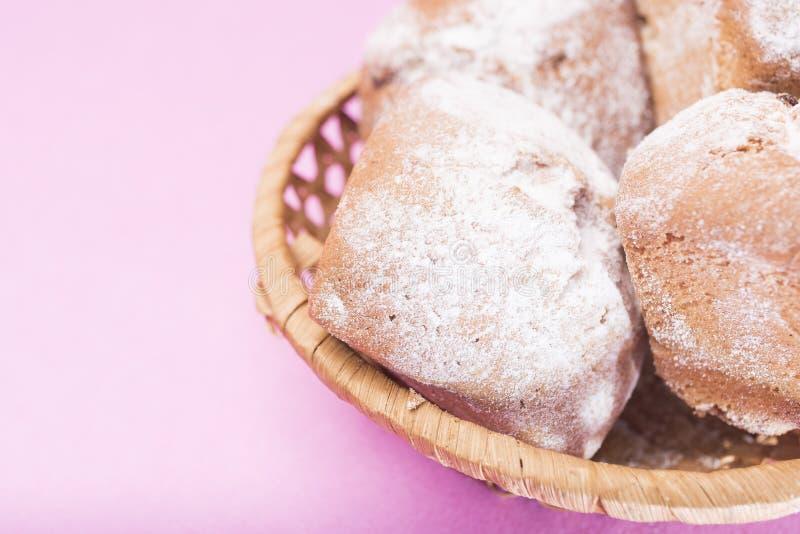 在一个柳条筐的自创松饼在轻轻地桃红色丁香背景 免版税库存照片