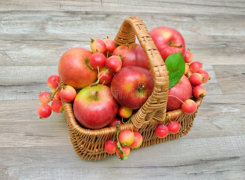 在一个柳条筐的苹果在木背景 免版税库存图片