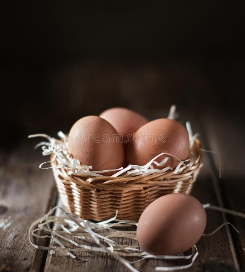 在一个柳条筐的鸡蛋在一张土气桌上 库存照片