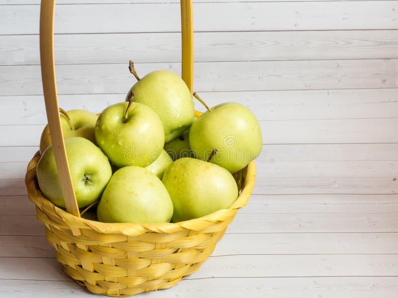 在一个柳条黄色篮子的绿色成熟苹果 免版税库存照片