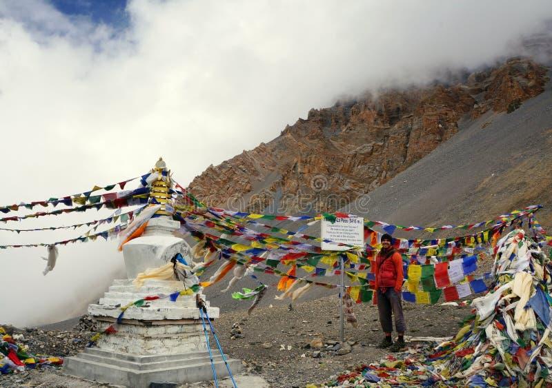 在一个标志附近的微笑的旅游立场在Thorong La的上面通过 喜马拉雅山 尼泊尔 图库摄影