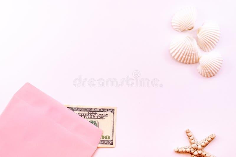 在一个桃红色信封的金钱,海星,在桃红色背景的贝壳 概念:休息的金钱 库存照片