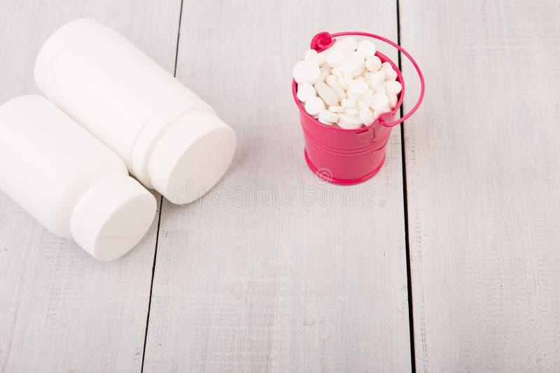 在一个桃红色桶和容器的许多不同的白色药片pil 库存照片